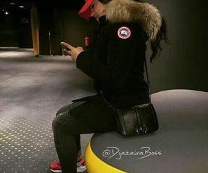 black purse, long wavy black hair, and red sneakers image