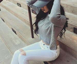 grey sweaters, grey baseball hat, and long wavy black hair image
