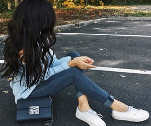 black purse, blue skinny jeans, and white sneakers image
