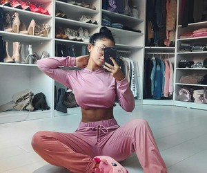 long black nails, pink sweatpants, and black top knot buns image