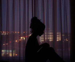Person sitting in front of a window in the dark.