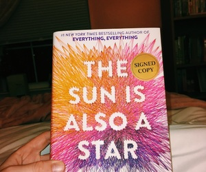 book, the sun is also a star, and reading image