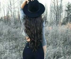 long wavy brown hair, black high waisted jeans, and grey crop long sleeve image