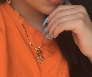 gold chains, gold hoops, and orange t-shirt image