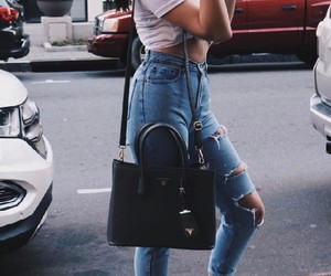 black purse, black ankle booties, and blue ripped jeans image