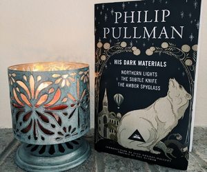 book, candle, and his dark materials image