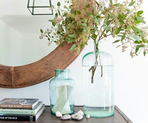 tabletop, books and flowers, and round mirror image