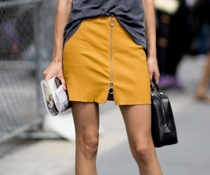 black purse, yellow ankle booties, and grey graphic t-shirt image