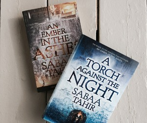 books, sabaa tahir, and a torch against the night image