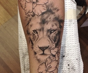 black ink, flower, and lion tattoo image