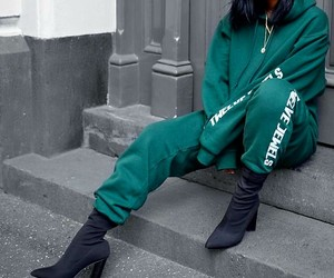 black ankle booties, short straight black hair, and dark green sweatpants image