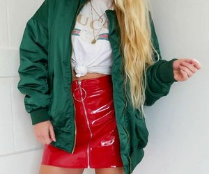 green bomber jacket, gold layered necklaces, and long wavy blonde hair image