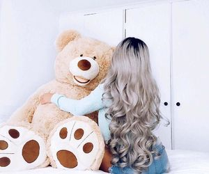 giant teddy bear, blue denim shorts, and long curled silver hair image