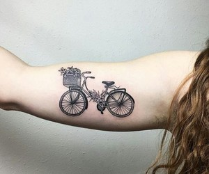 tattoo, bicycle, and arm image