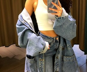long wavy brown hair, light blue jeans, and oversized denim jacket image