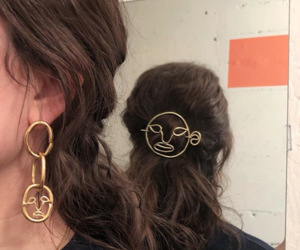 brooch, brown hair, and gold earrings image