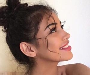 big lips, curly hair, and messy bun image