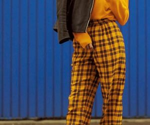 white sneakers, yellow plaid pants, and black leather jacket image