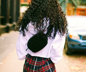 long brown curly hair, black fanny pack, and red plaid pants image