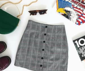 white graphic t-shirts, brown glasses, and grey plaid skirts image