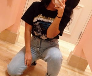 light blue jeans, black graphics t-shirts, and long wavy black hair image