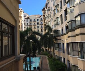 buildings, trees, and poolside image