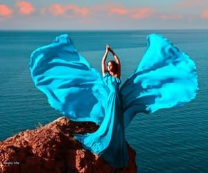 redhead turquiose dress and sea rocks clouds image