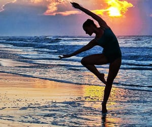 Silhouette of a Ballet Dancer Posing at Early Dawn on a Tropical Island Beach.