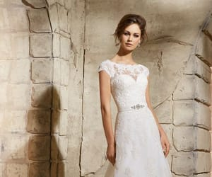 Timeless and elegant, this slim A-line wedding dress combines a classic bateau neckline and delicate embroidered lace. The stunning illusion back is adorned in