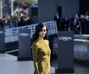model presents a creation, catwalk installed, and barge on the seine river image
