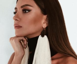 black hair, tanned skin, and statement earrings image