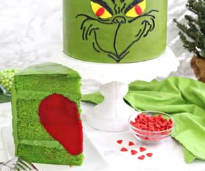 Grinch Cake - this showstopping green Grinch Cake is decorated with a perfectly Grinchy face, and has a wonderful secret--a red heart on the inside! | From SugarHero.com