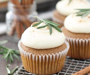 Three gorgeous gingerbread cupcakes with white cupcake wrappers and a rosemary garnish are sitting on a wire baking rack with cinnamon stick