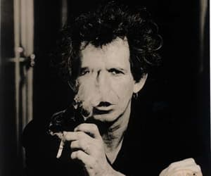 Keith Richards, guitar slinger, and rolling stone sitting image