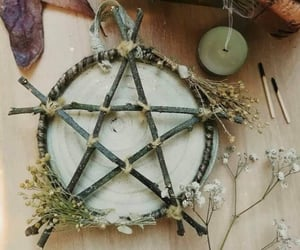 candle, dried flowers, and witchy image