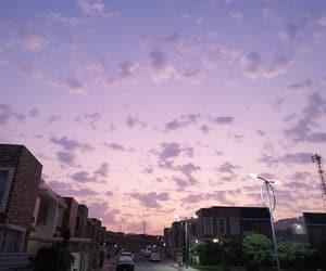 city view, purple sky, and sun image