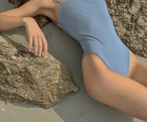 blue and muted swimsuit laying image