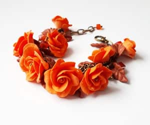 charm bracelet, orange bracelet, and flower bracelet image