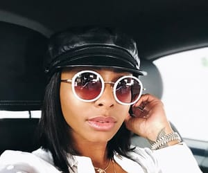 round sunglasses, white blouse, and selfie image