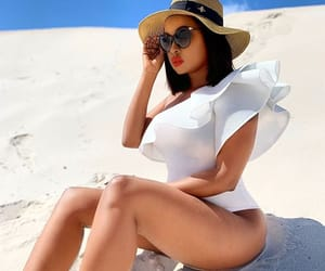 hat, white bodysuit, and white sand image
