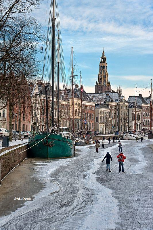 frozen canal and groni̇ngen-netherlands image