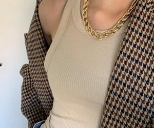 denim jeans, beige coat, and gold chain necklace image