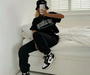 black hat, black shirt, and black sneakers image