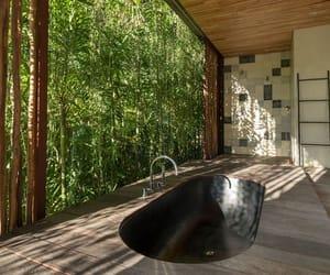 In this modern bathroom, a black sunken bathtub surrounded by wood is positioned for relaxing tropical garden views. #SunkenBathtub #BlackBathtub #TropicalBathroom #ModernBathroom