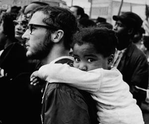 A white man carries a black girl on his shoulders during a march with Dr. Martin Luther King, Jr. Alabama, ca. 1965.