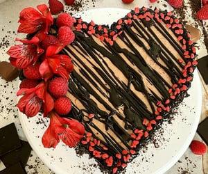 Cuore cioccolatoso, di pan di Spagna, glassa cioccolato fondente colato. Abbellita con fiori e lamponi