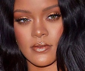 Rihanna with gold shimmer eyeshadow on her upper lids, bronze shimmer on her under lid, hues of brown & peach blended on the outer corner of her eyes. Peach blush & light pink shimmer lips. Riri is makeup goals!