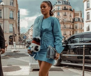 Rihanna in blue mini dress and strappy silver heels in Paris. Riri has her hair styled up in a ponytail.