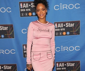 Rihanna wore a pink Adam Selman dress with the word 'Spoiled' written across the front and costumised Puma sneakers by Mr Completely as she attended the NBA All-Star Weekend at Barclay's Center in Brooklyn, New York on Saturday.