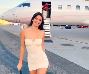 Kendall Jenner - celebrity icon walking off an airplane in style with beige spaghetti strap mini dress and off white cowboy boots. Image via her Instagram - I love to see her day to day pics.